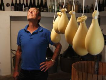 Nella sua cantina Località Giuncana - Comune di Viddalba  Ritratto in cantina ingombra di  damigiane, bottiglie, un torchio e formaggio appeso ad esiccare