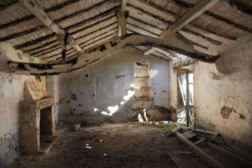 """La """"Trai Tolta"""" Località Sangainu - Comune di Palau  Stazzu Faulagghju. Interno di stazzo abbandonato. Trave portante di legno, ed il tetto in canne e ginepro ancora intatto"""