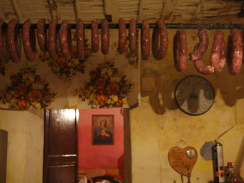 N.S. di li Salticci Località Maltineddu - Comune di Palau  Stazzu Maltineddu. Salsicce appese ad essiccare, sullo sfondo stanza da letto con quadro dell'addolorata