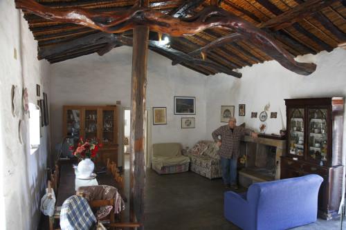 """Tra li """"Trai Tolti"""" Località Valle del Liscia - Comune di Palau  Stazzu La Isgiola. Giovanni Maria Cuccu all'interno del suo stazzo, con tetto di canne e di ginepro, pavimento in cemento lucidato"""